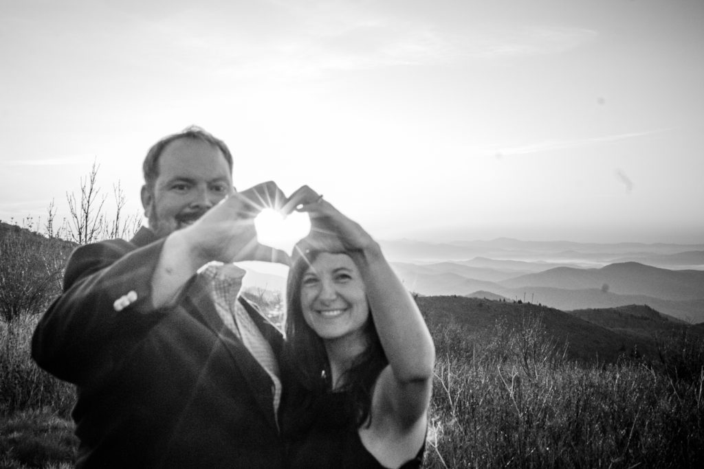 The couple makes a heart for the sun to create a sunflare.