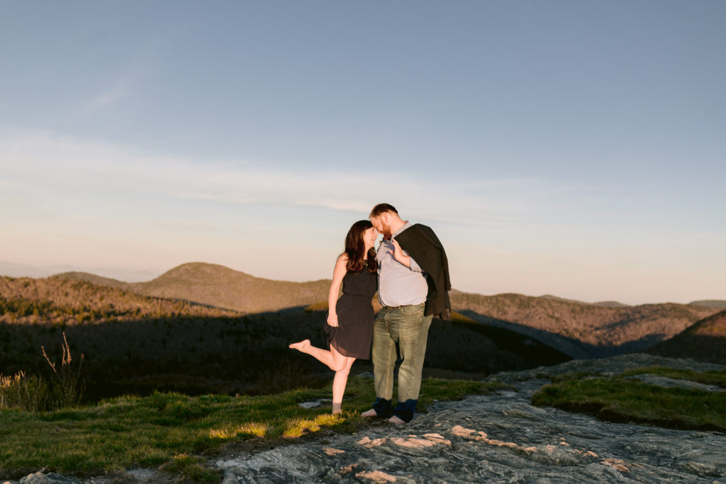 Sunny engagement photos on top of a mountain at sunrise.