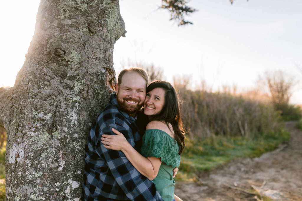 Sunrise engagement session at Black Balsam with trees and tall grass.