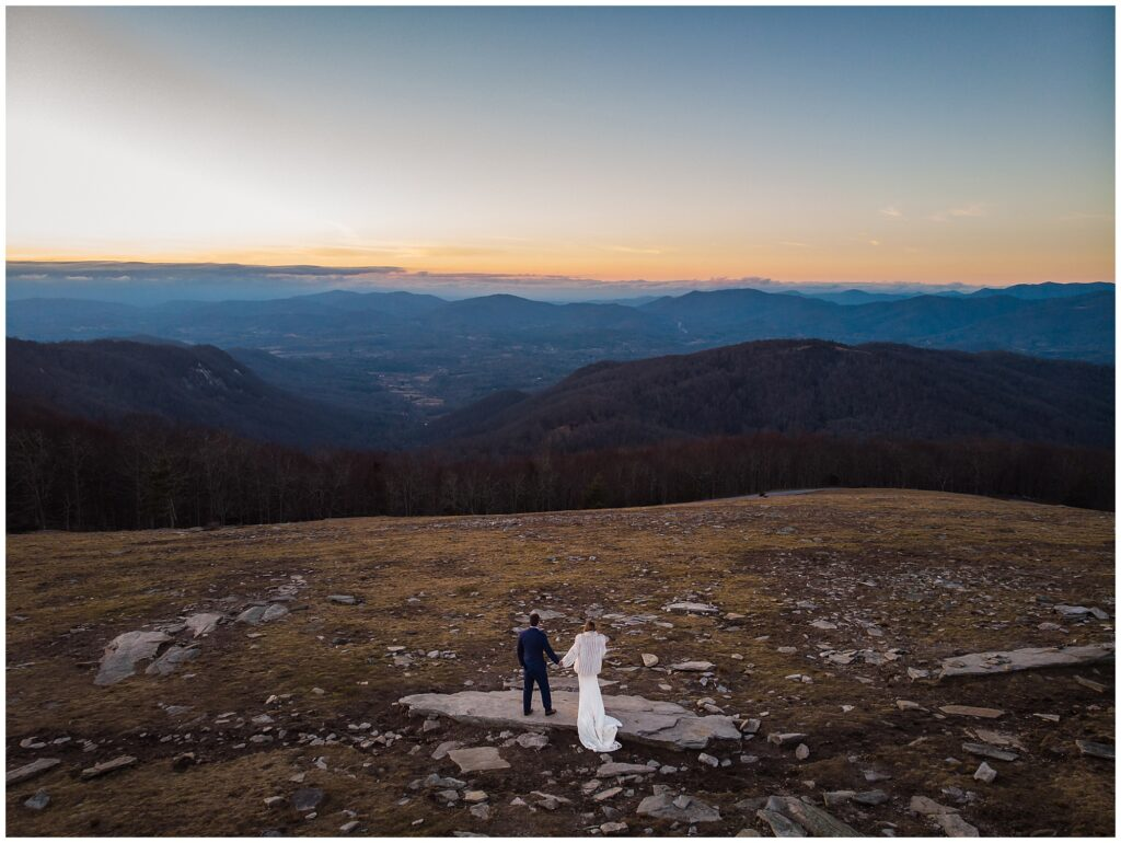 A drone photo of the sunset at Bearwallow mountain with the bride and groom in the distance.