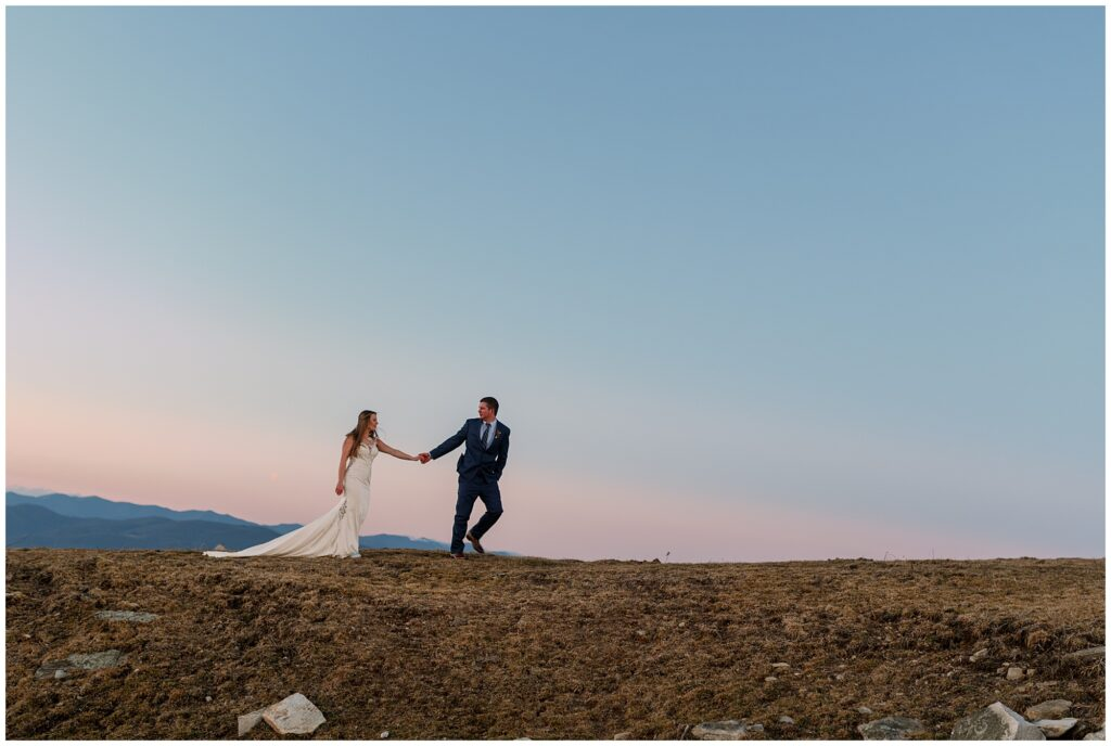 The groom leads his bride up the hill at Bearwallow mountain after their winter elopement ceremony.
