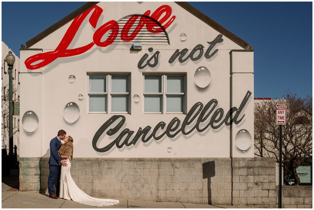 The bride and groom visited the famous love is not cancelled art mural at Spicer Green Jewelry in Asheville during their pandemic elopement.