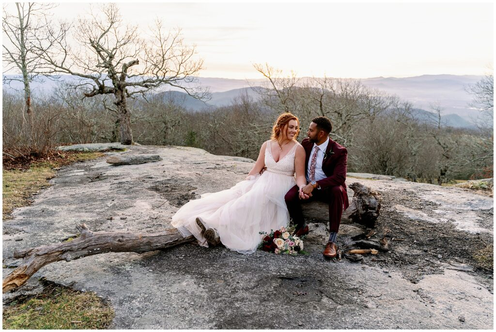 bride and groom sit on a rock and enjoy the mountain top views of bearwallow
