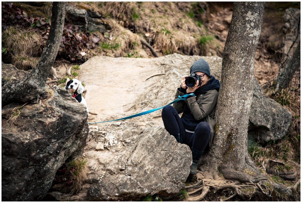 A behind the scenes photo of our Legacy and Legend team member capturing the shot on the rocks and holding the dog.