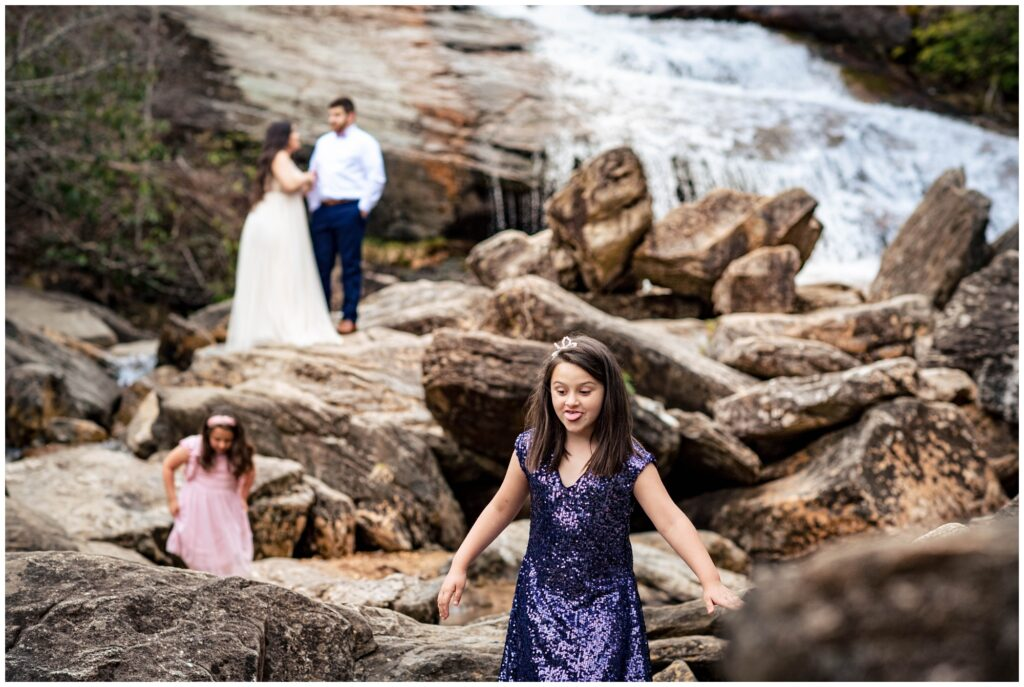 Silly family photos during an adventure session at a waterfall.