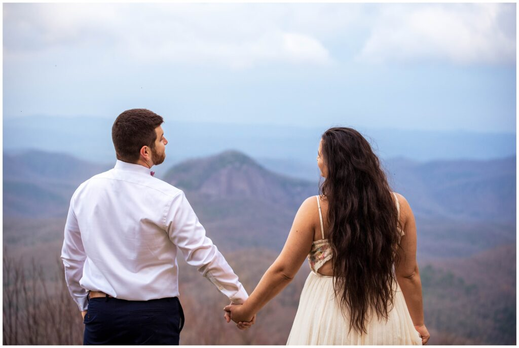 Couples photo of them holding hands looking out at the view of mountains.