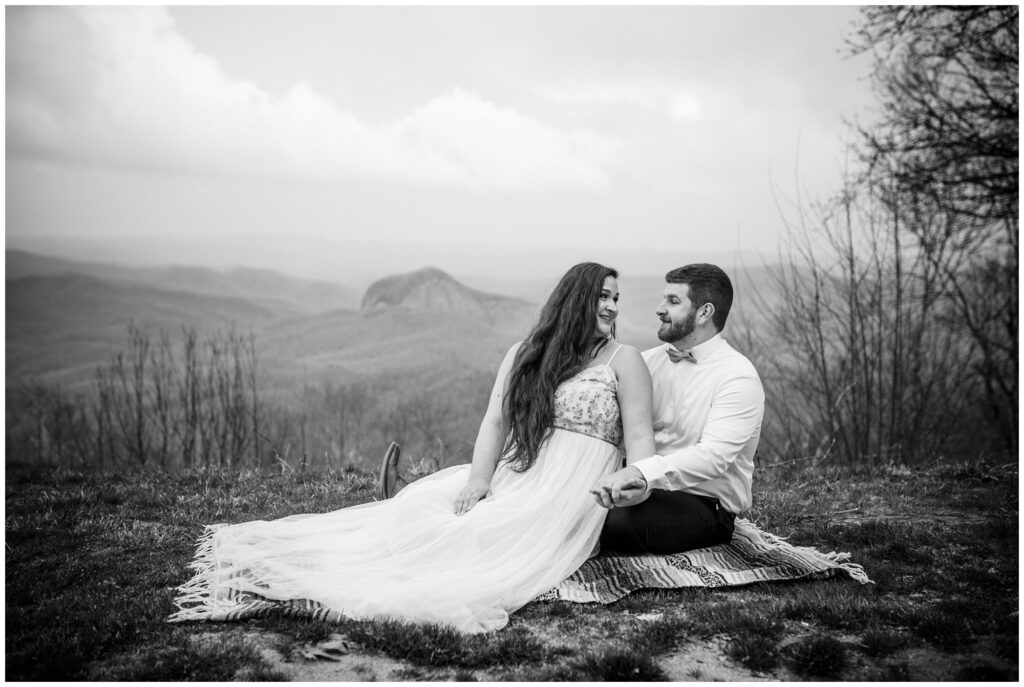 The newlyweds sit on a blanket together on top of the mountain.