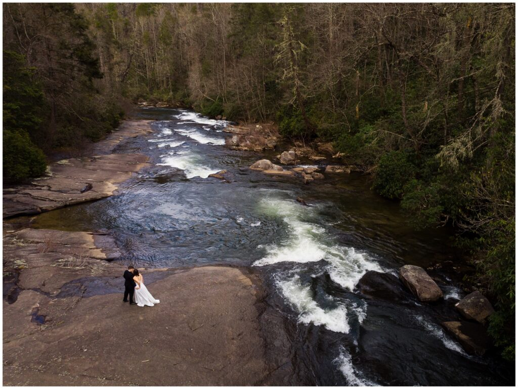 Drone photo of the couple together next to a waterfall and river.