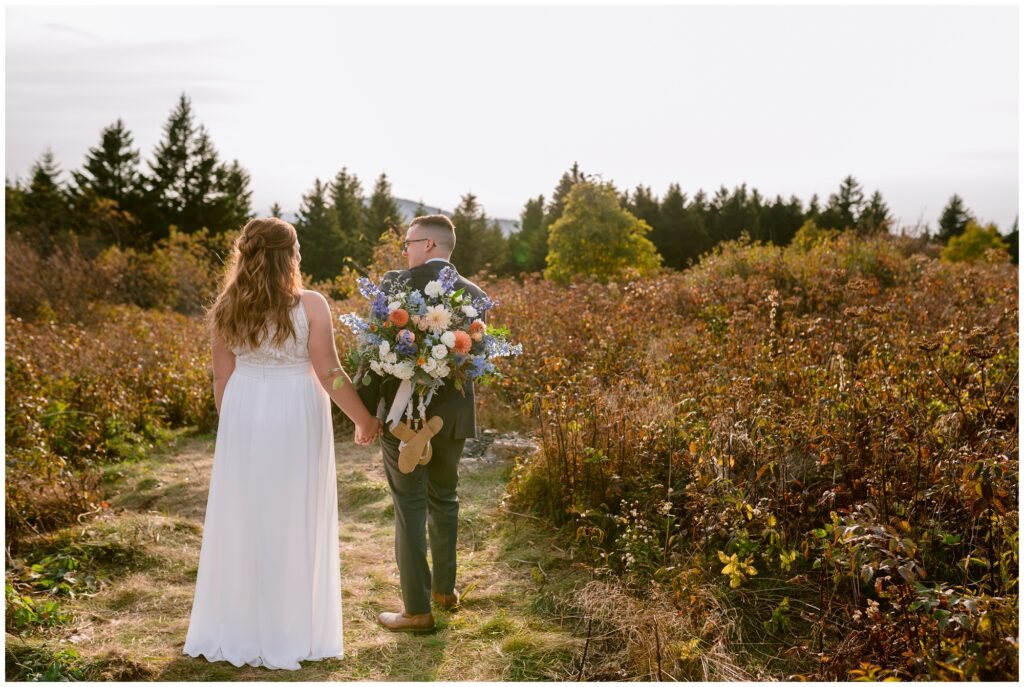 The groom carries the fall bridal bouquet and sandals in a backpack up the mountain.