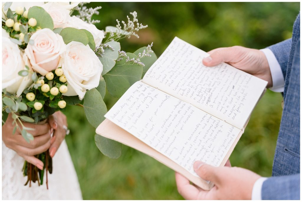 A groom holds open his vow book to read during their elopement.